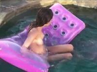 Купается в бассейне на матрасе